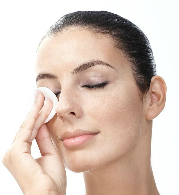 Young woman removing eye makeup by cotton pad eyes closed.